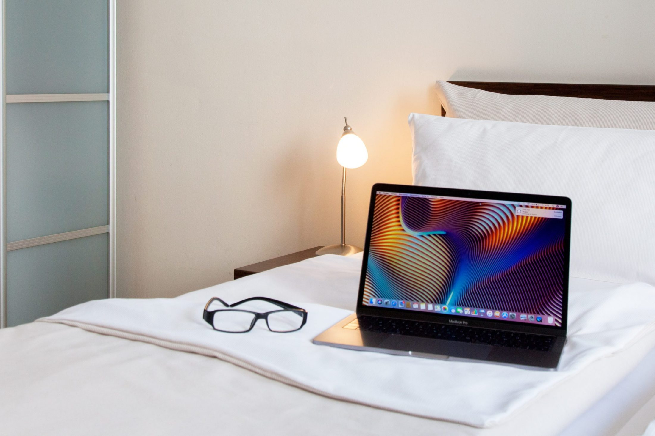 Laptop on bed in serviced apartment Frankfurt